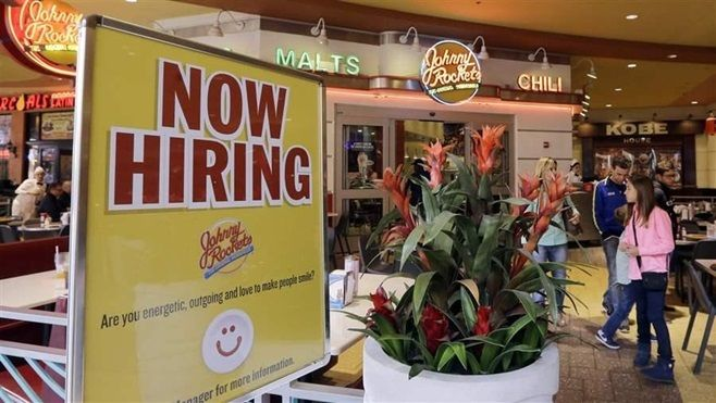 A restaurant in Miami advertises for more employees. In many states, the growing demand for service workers is prompting pay