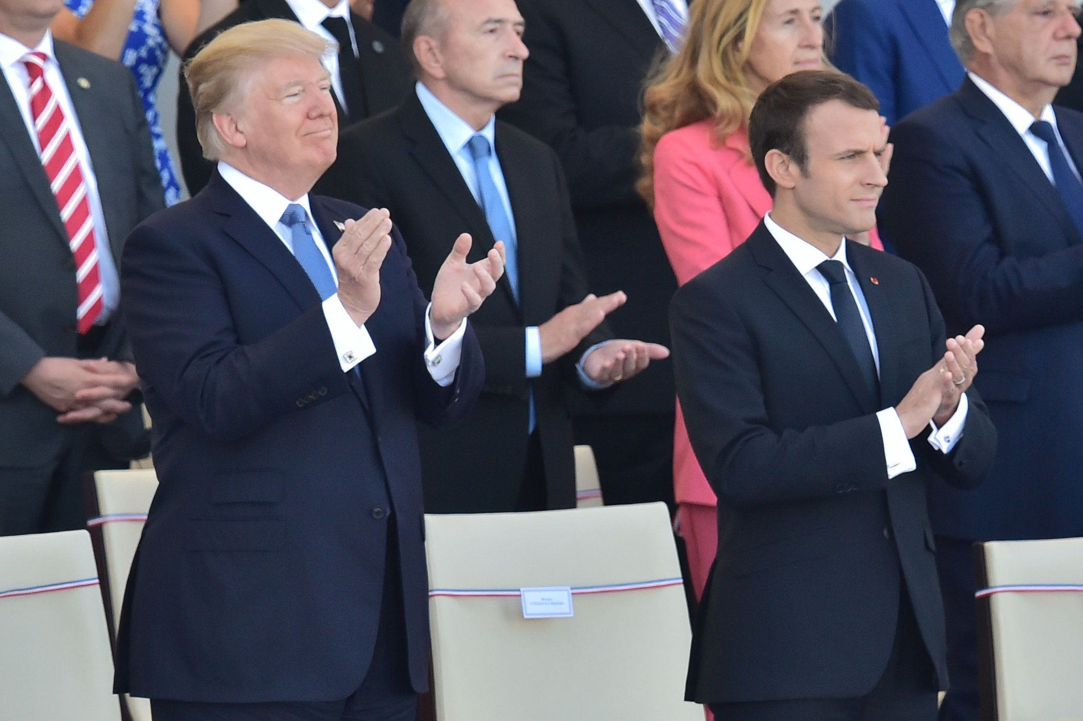 US President Donald Trump (L) and his French counterpart Emmanuel Macron applaud as they watch the annual Bastille Day military parade on the Champs-Elysees avenue in Paris on July 14, 2017. The parade on Paris's Champs-Elysees will commemorate the centenary of the US entering WWI and will feature horses, helicopters, planes and troops. / AFP PHOTO / CHRISTOPHE ARCHAMBAULT        (Photo credit should read CHRISTOPHE ARCHAMBAULT/AFP/Getty Images)