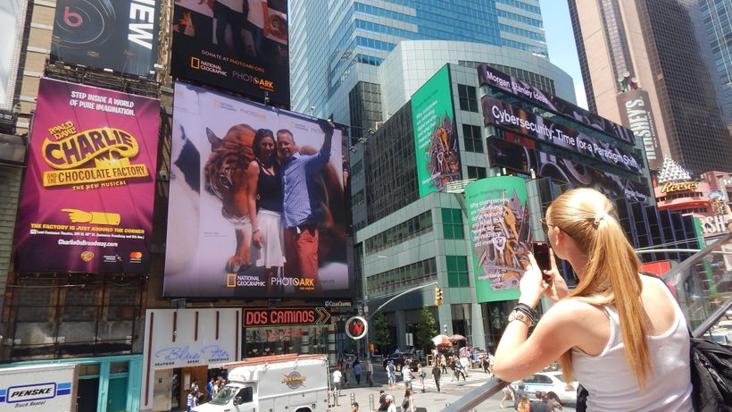 Woman in Times Square takes a photo of her #SaveTogether selfie on a digital billboard.