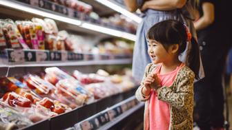 Excited lovely little girl shopping for fruits with mom in the supermarket