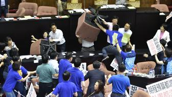 Ruling Democratic Progressive Party (DPP) legislators Cheng Yun-peng (centre L) and Wu Ping-jui (centre R, obscured by chair) brandish chairs while facing demonstrating main opposition Kuomintang (KMT) and People First Party (PFP) legislators calling for a boycott of the forward-looking project at the Parliament in Taipei on July 14, 2017. Taiwan's parliament descended into chaos for a second day on July 14 with lawmakers wielding office chairs at each other and throwing water balloons as they clashed over a controversial infrastructure project.  / AFP PHOTO / SAM YEH        (Photo credit should read SAM YEH/AFP/Getty Images)