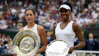 LONDON, ENGLAND - JULY 15:  Garbine Muguruza of Spain celebrates victory with the trophy alongside runner up Venus Williams of The United States after the Ladies Singles final on day twelve of the Wimbledon Lawn Tennis Championships at the All England Lawn Tennis and Croquet Club at Wimbledon on July 15, 2017 in London, England.  (Photo by Shaun Botterill/Getty Images)