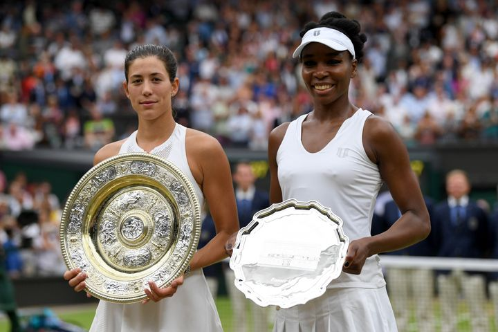 Garbine Muguruza of Spain celebrates victory with the trophy alongside runner up Venus Williams of The United States after th