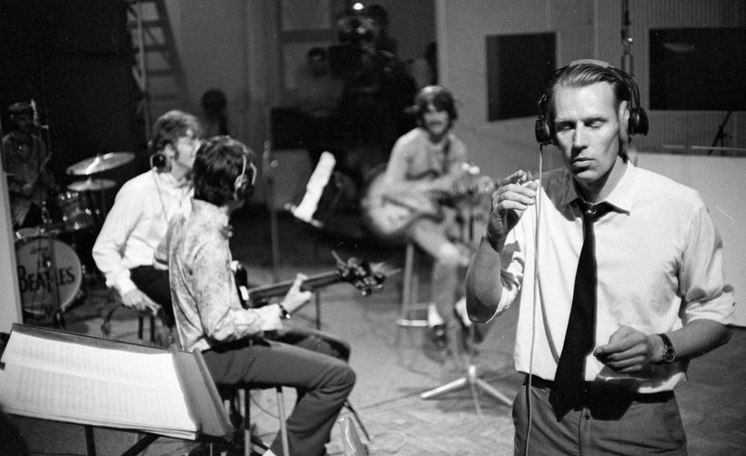 "George Martin (foreground) and the Beatles rehearsing ""All You Need Is Love"" in June 1967"