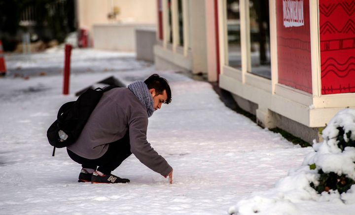 A man touches the snow.