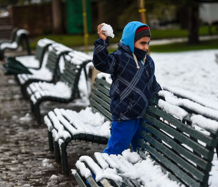 A child prepares to launch a snowball.