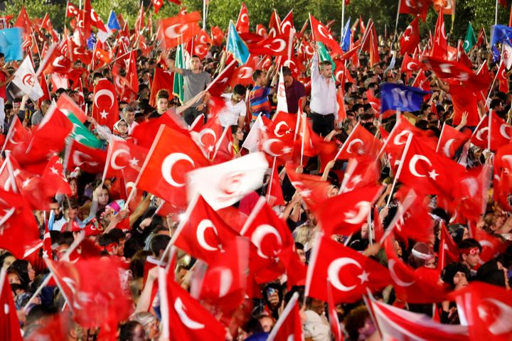 People wave Turkey's national flags as they attend a ceremony marking the first anniversary of the attempted coup in front of
