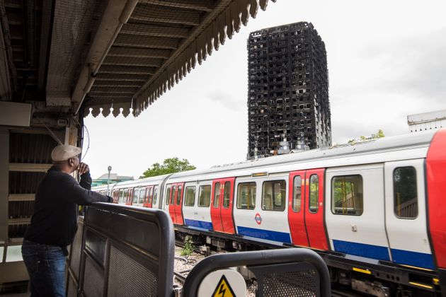 A tube train runs past the remains of the Grenfell Tower, a month after fire engulfed the 24-storey block...