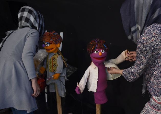 In this photograph taken on July 2, 2017, Afghan puppeteers dress Sesame Street Muppets Zeerak (left)...