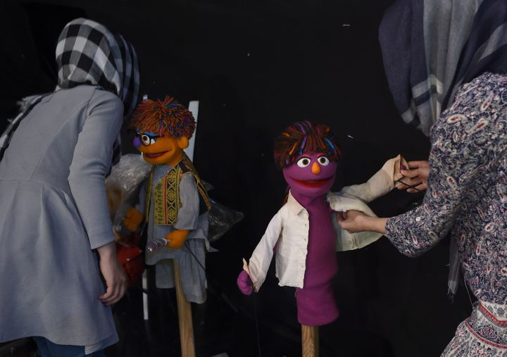 In this photograph taken on July 2, 2017, Afghan puppeteers dress Sesame Street Muppets Zeerak (left) and Zari ahead of