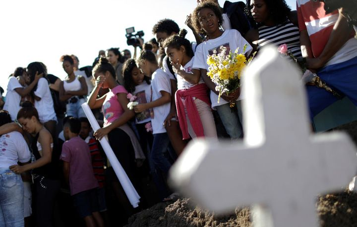 Children mourn the death of a ten-year-old girl killed in crossfire between police and drug dealers in Rio, July 6 2017.