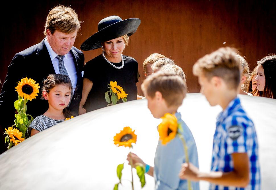 King Willem-Alexander and his wife Queen Maxima of the Netherlands pay their respects at the memorial.