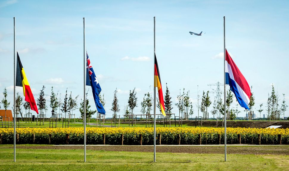 Flags are seen at half mast during an event to unveil a national monument to commemorate the victims of the Malaysia Airlines