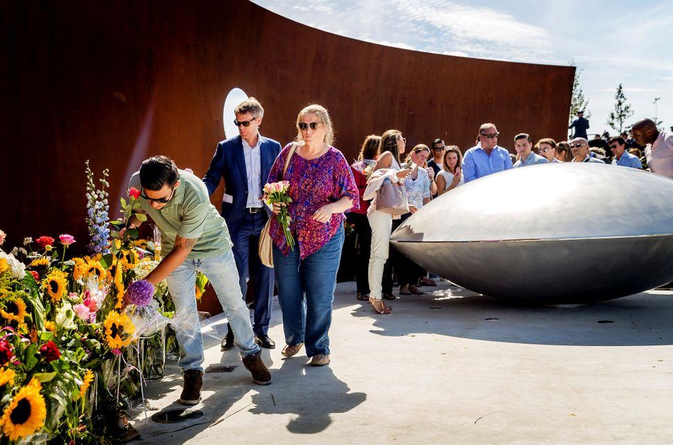 Relatives of the victims leave flowers at the new monument.