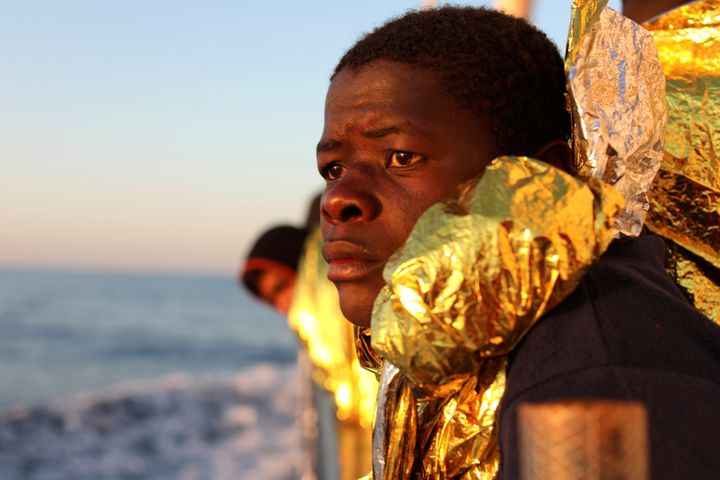 A migrant, covered with a thermal blanket, gazes at the sea aboard a boat operated by the Spanish NGO Proactiva Open Arms fol