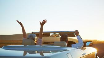 Rear view shot of a happy couple in a car excited about the sun rise