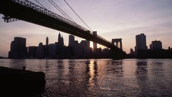 (Original Caption) 7/14/1977-New York: View of New York City skyline and Brooklyn Bridge during blackout, with no lights remaining on. Buildings are silhouetted by sunset.