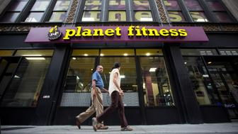 Pedestrians walk past a Planet Fitness Inc. gym in New York, U.S., on Sunday, Aug. 30, 2015. Planet Fitness Inc. is scheduled to release second quarter earnings results after the close of U.S. financial markets on Sept. 2. Photographer: Michael Nagle/Bloomberg via Getty Images