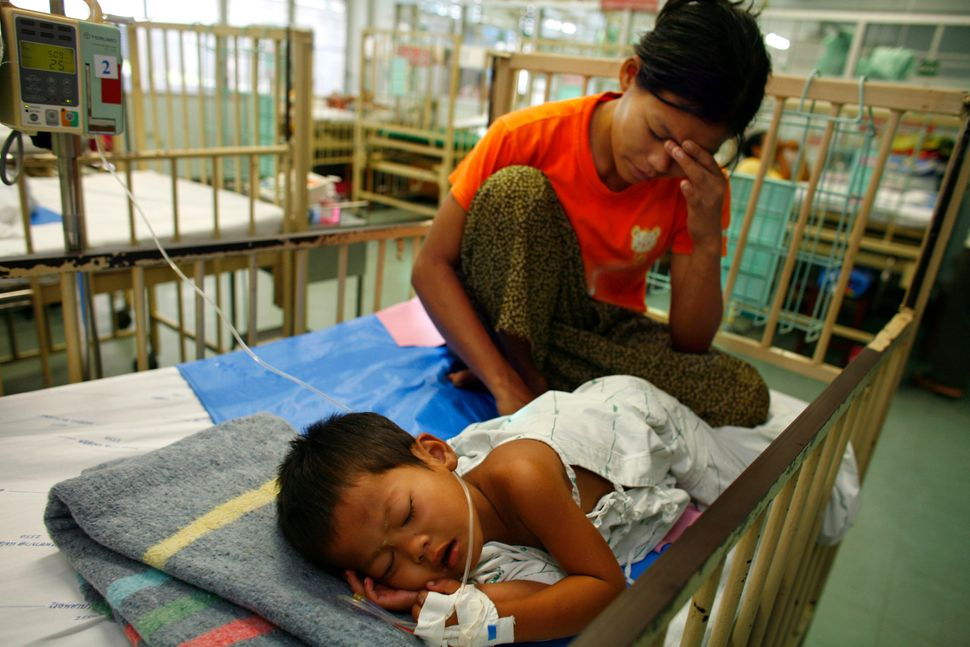 A woman from Myawaddy, Myanmar, sits with her son suffering from dengue fever in Mae Sot, Thailand, on Oct. 30, 2007.