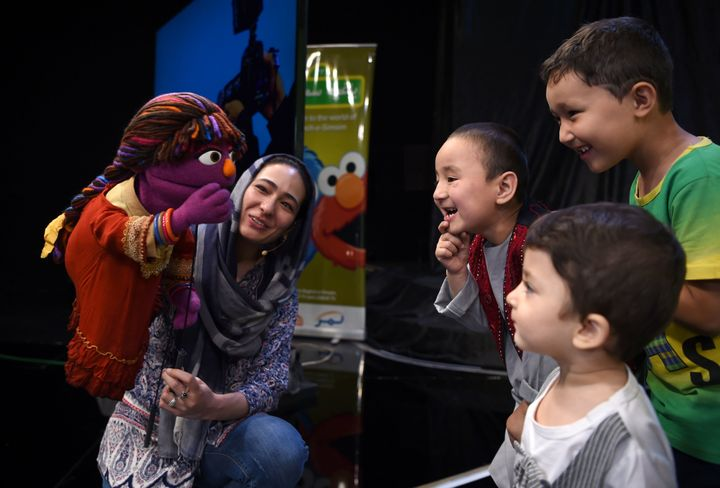 In this photograph taken on July 2, 2017, Afghan children meet Sesame Street Muppet 'Zari' after a recording at a television
