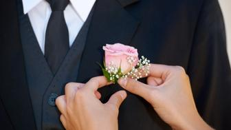 Cropped image of a groom getting his boutonniere adjusted before the wedding ceremony