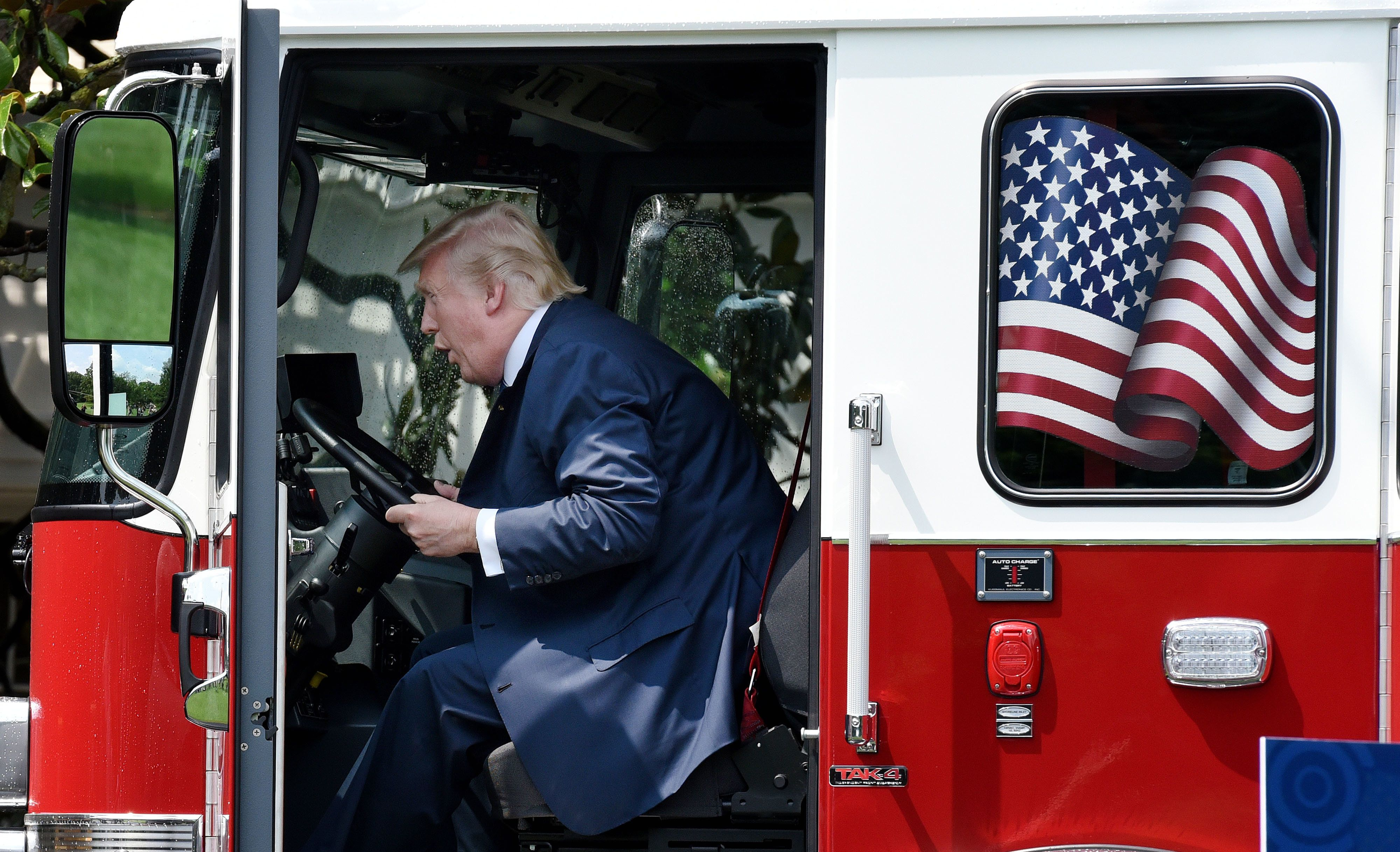 President Donald Trump examines a fire truck from Wisconsin-based manufacturer Pierce on the South Lawn during a 'Made in America' product showcase event at the White House in Washington, DC, on July 17, 2017.  / AFP PHOTO / Olivier Douliery        (Photo credit should read OLIVIER DOULIERY/AFP/Getty Images)