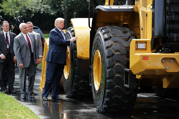 Trump admires a wheel loader made by Caterpillar.