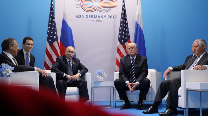 Russian President Vladimir Putin, third from left, sits next to President Donald Trump at a G20 summit meeting in German