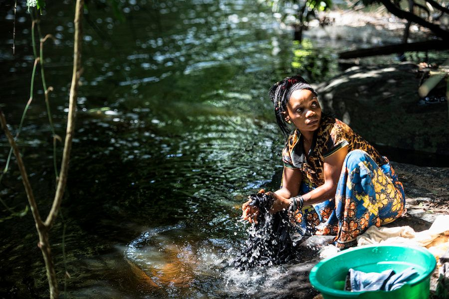 Regine Bora washes clothes by the river while black flies buzz around her.