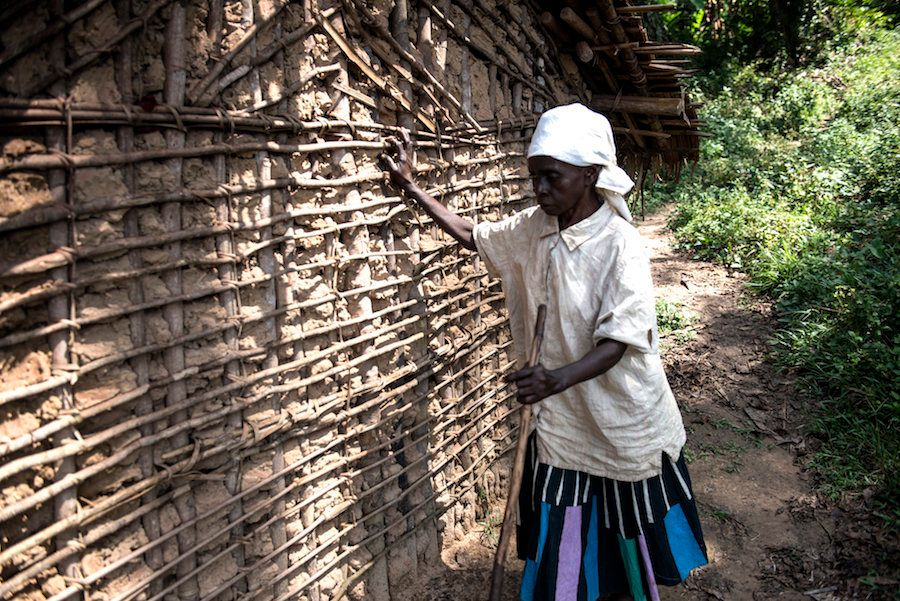 Mapuani, who lost her vision to river blindness, feels her way to the outhouse.