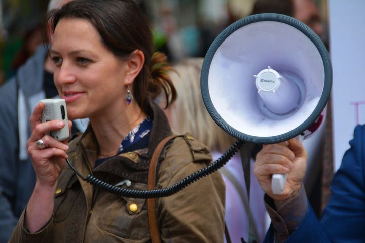 <p>SIGNAL BOOST: A male ally holds a megaphone.</p>