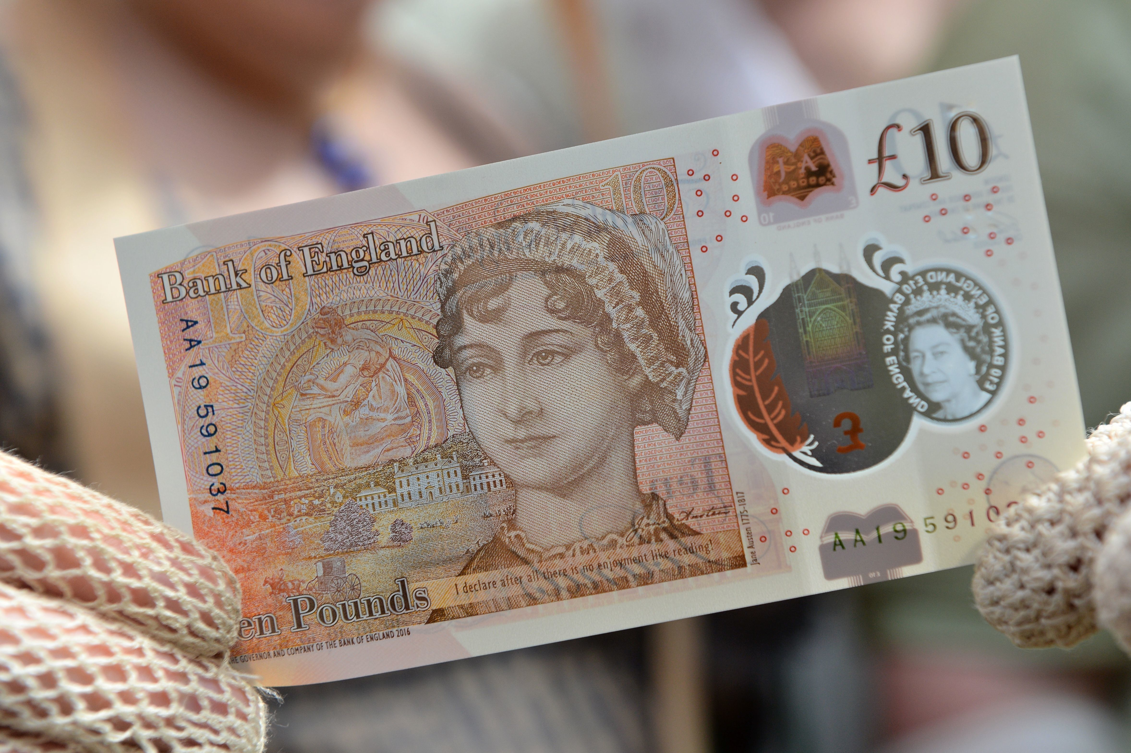 People in period costume pose with on the Bank of England's new ten pound notes, featuring author Jane Austen, during its launch at Winchester Cathedral in Winchester, southern England, on July 18, 2017. Two hundred years after Jane Austen's death, Britain is celebrating one of its best-loved authors, who combined romance with biting social commentary that still speaks to fans around the world. Austen is buried in the cathedral in Winchester, where she died. / AFP PHOTO / POOL / Chris J Ratcliffe        (Photo credit should read CHRIS J RATCLIFFE/AFP/Getty Images)