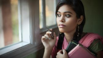 Indoor, day time, close-up image of serene Asian teenager girl student with long and black braided hair sitting near window under natural light wearing traditional Indian dress (Salwaar Kameez, Dupatta). She is thinking deeply and looking away at something outside window with sadness and blank expression on her face holding books and pen. One person, waist up, horizontal composition with copy space and selective focus.