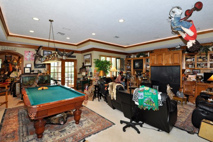 Family room with mannequin on a tricycle hanging from ceiling.