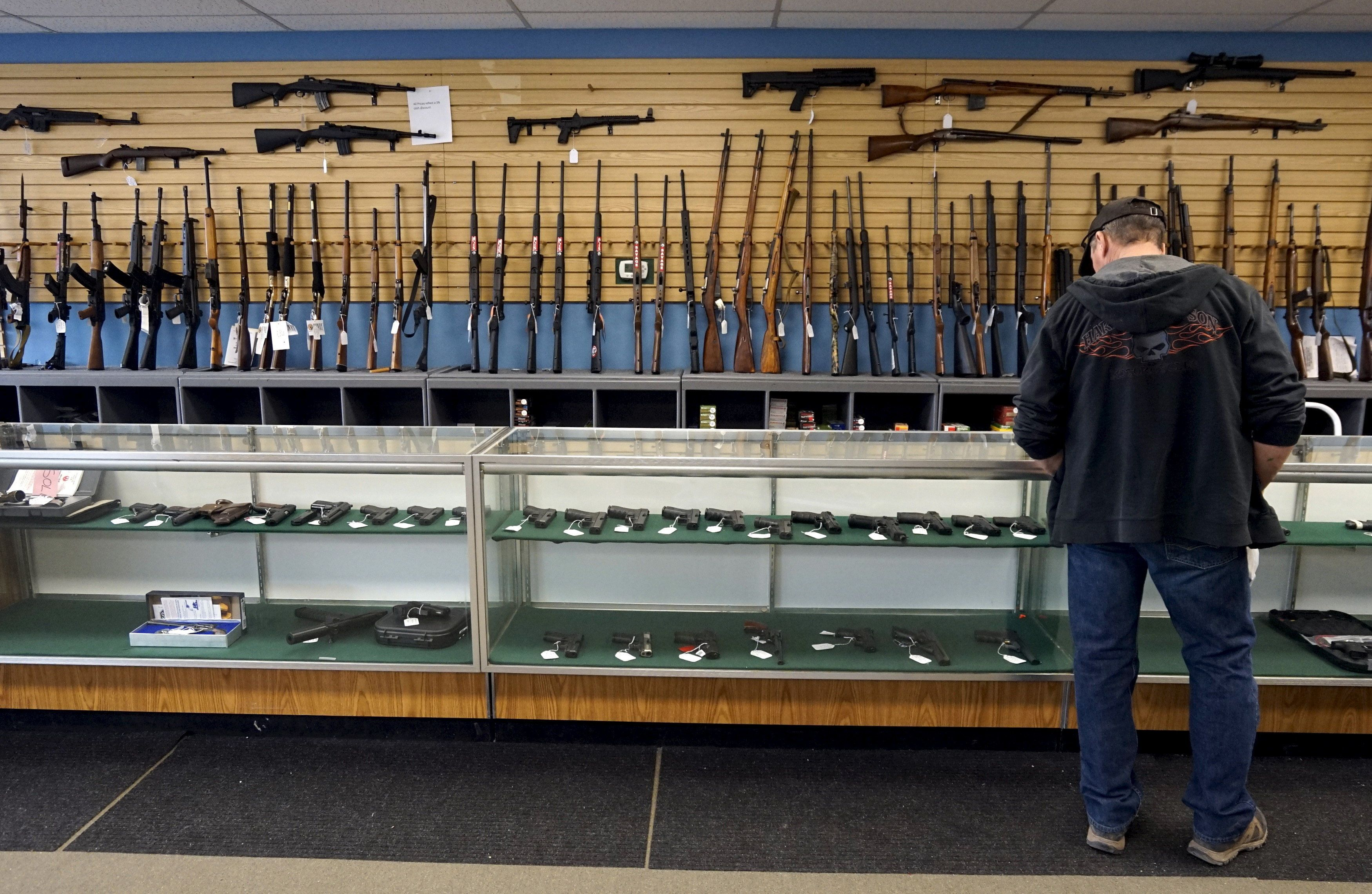 A customer looks over weapons for sale at the Pony Express Firearms shop in Parker, Colorado December 7, 2015. Many Americans are stocking up on weapons after the country's worst mass shooting in three years. Gun retailers are reporting surging sales, with customers saying they want to keep handguns and rifles at hand for self-defense in the event of another attack. REUTERS/Rick Wilking