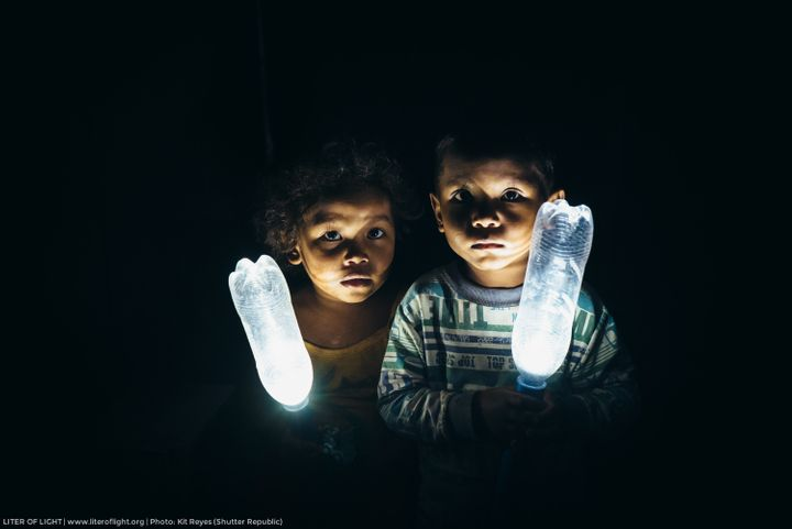 Two kids holding Liter of Light bottles with a solar-powered LED inside.