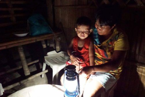 A family sitting by a solar-converted kerosene lamp from Liter of Light.