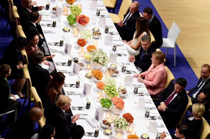 German Chancellor Angela Merkel (c-R) flanked by (from L) Russia's President Vladimir Putin, US First Lady Melania Trump, Argentinia's President Mauricio Macri and China's President Xi Jinping attends the banquet after a concert at the Elbphilharmonie concert hall during the G20 Summit in Hamburg, Germany, on July 7, 2017.