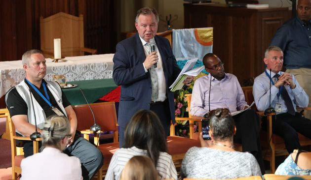 Barry Quirk (centre) speaks during a public meeting between Grenfell residents and authorities at the...