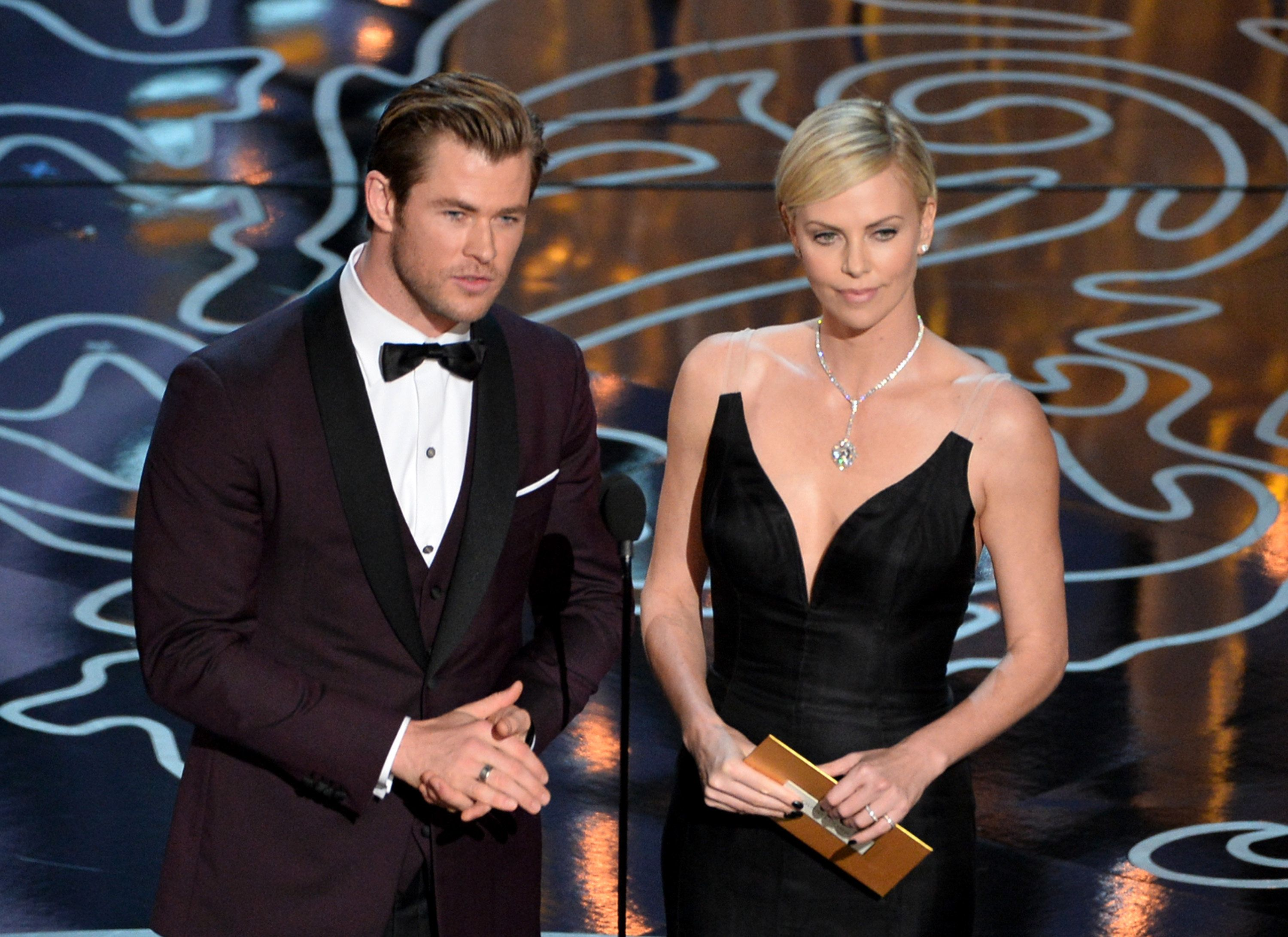 HOLLYWOOD, CA - MARCH 02:  Actors Chris Hemsworth (L) and Charlize Theron speak onstage during the Oscars at the Dolby Theatre on March 2, 2014 in Hollywood, California.  (Photo by Kevin Winter/Getty Images)