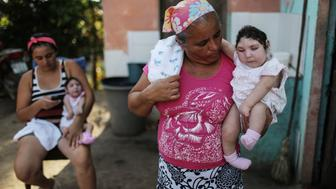 AREIA, BRAZIL - DECEMBER 25:  Mother Raquel Barbosa holds her daughter Eloa (L) as grandmother Maria Jose carries twin daughter Eloisa, both 8 months old and both born with microcephaly, at a Christmas gathering at Maria Jose's home on December 25, 2016 in Areia, Paraiba state, Brazil. Mother Raquel said she contracted Zika during her pregnancy. As many of the babies born with microcephaly, believed to be linked to the Zika virus, approach or have turned one year old in the region, doctors and mothers are adapting and learning treatments to assist and calm the children. Many suffer a plethora of difficulties including vision and hearing problems with doctors now labeling the overall condition as congenital Zika syndrome. Authorities have recorded thousands of cases in Brazil in which the mosquito-borne Zika virus may have led to microcephaly in infants. Microcephaly results in an abnormally small head in newborns and is associated with various disorders.  (Photo by Mario Tama/Getty Images)