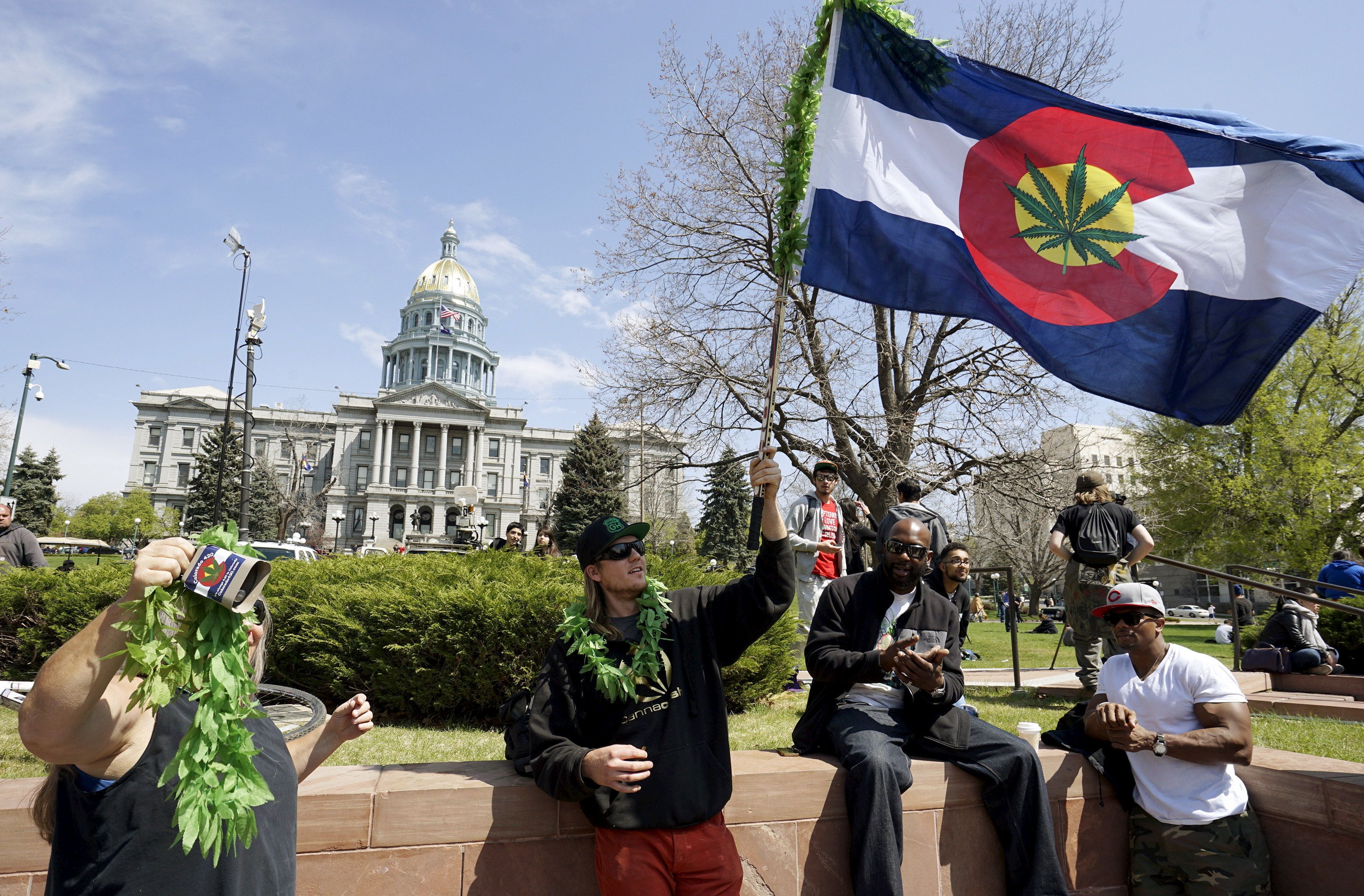 A man waves a Colorado flag with a marijuana leaf on it at Denver's annual 4/20 marijuana rally in front of the state capitol building in downtown Denver April 20, 2015. Colorado was the first state in the nation to legalize recreational marijuana in 2012. REUTERS/Rick Wilking