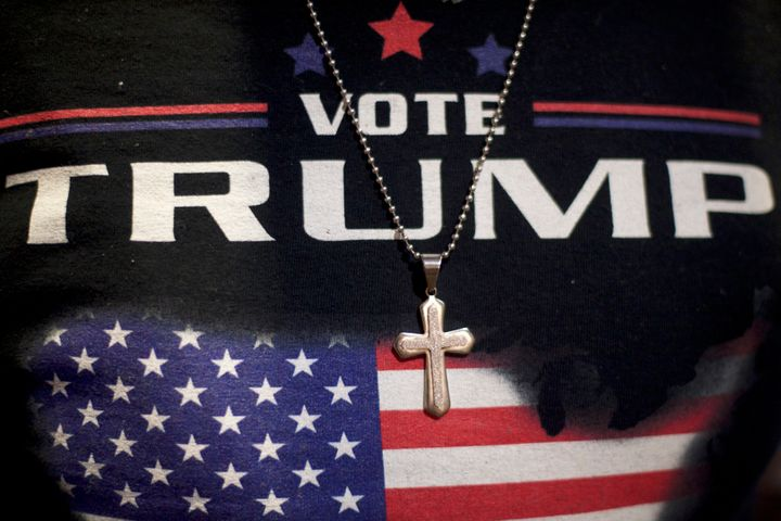 A Christian minister wears a Donald J. Trump-themed shirt with a cross necklace before a 2016 campaign event in Get