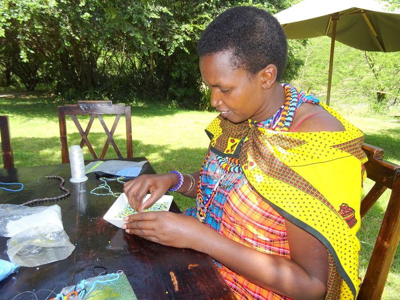 <em>Doreen Sekento Kumum teaches us how to make bead necklaces</em>
