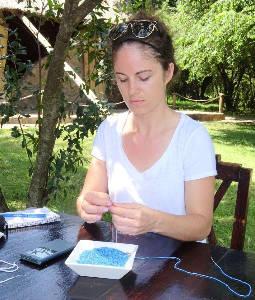 <em>Katie Rees stringing beads</em>
