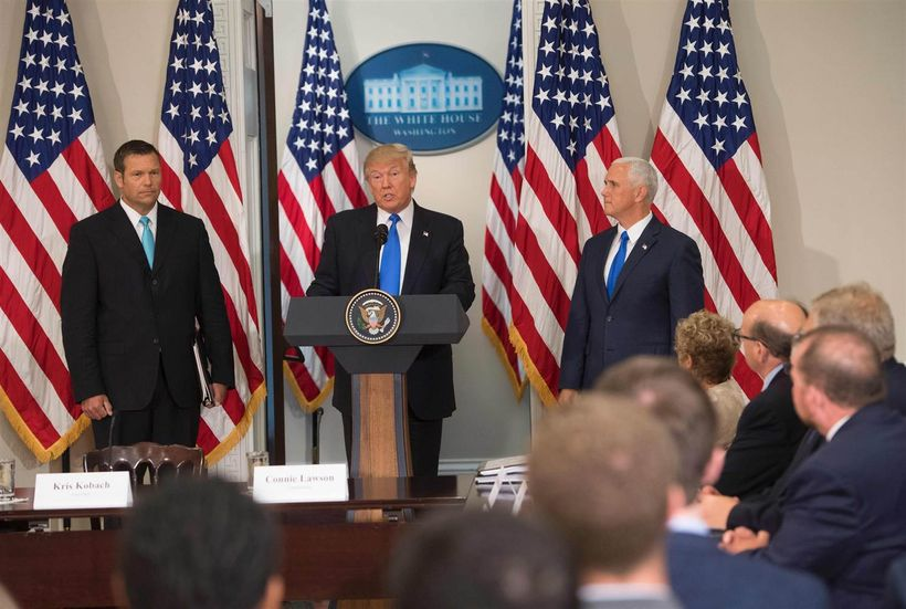 Trump speaks alongside Kansas Secretary of  State Kris Kobach, left, and Vice President Mike Pence during the first  meeting