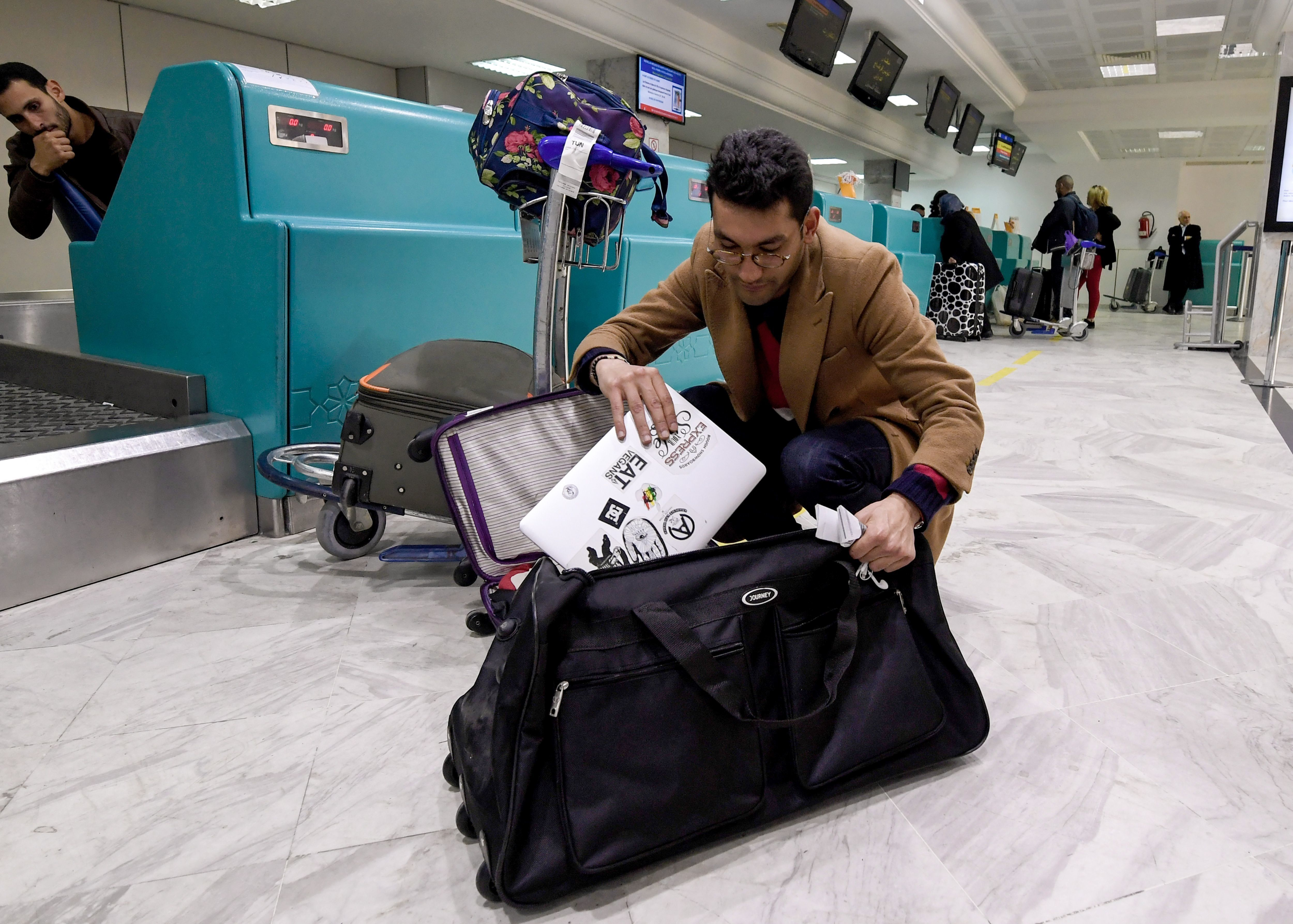 A Libyan traveller packs his laptop in his suitcase before boarding his flight for London at Tunis-Carthage International Airport on March 25, 2017. The United States this week announced a ban on all electronics larger than a standard smartphone on board direct flights out of eight countries across the Middle East, in effect from March 25, 2017. US officials would not specify how long the ban will last, but Emirates told AFP that it had been instructed to enforce the measures until at least October 14. Britain has also announced a parallel electronics ban targeting all flights out of Egypt, Turkey, Jordan, Saudi Arabia, Tunisia and Lebanon. / AFP PHOTO / FETHI BELAID        (Photo credit should read FETHI BELAID/AFP/Getty Images)