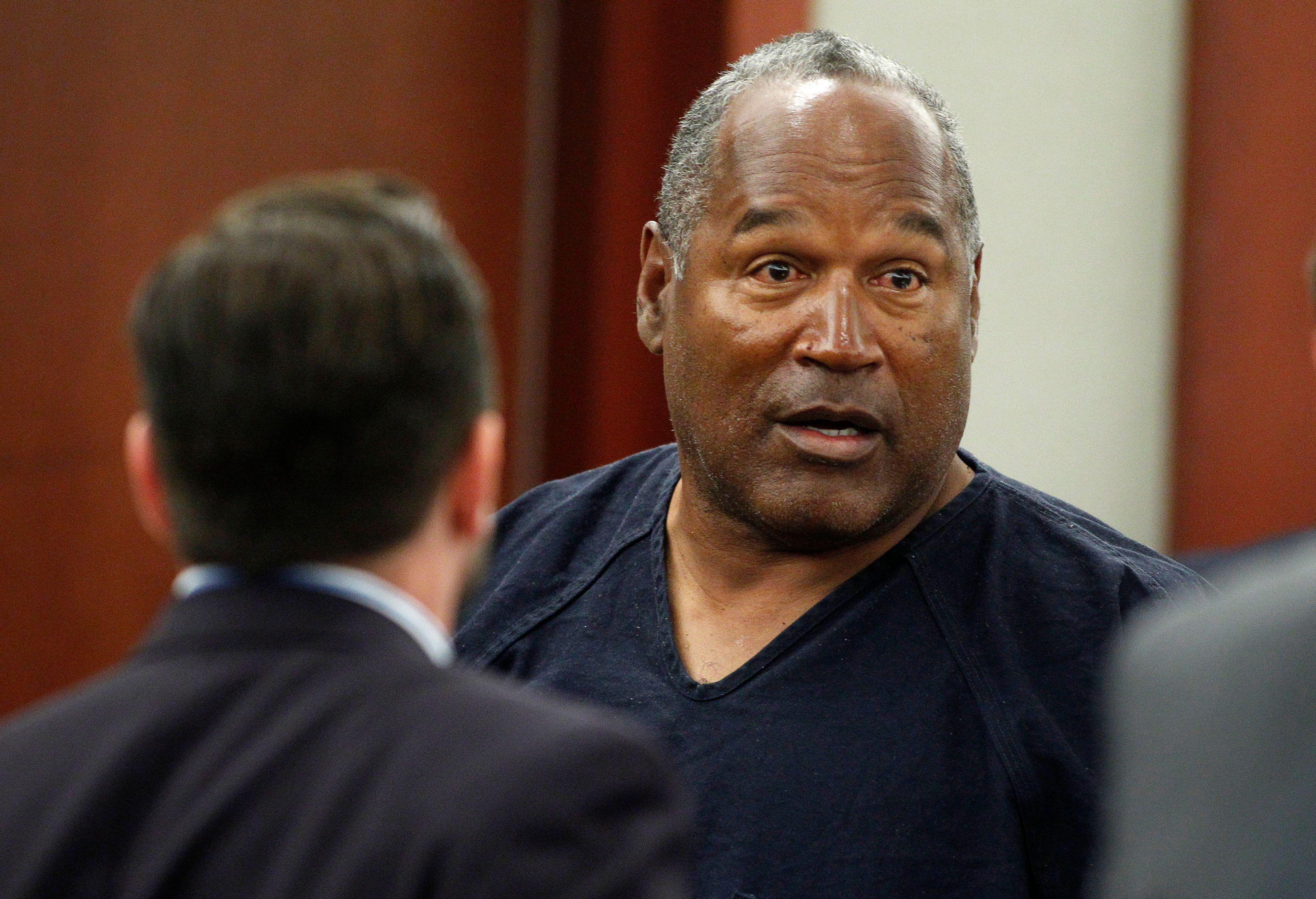 VEGAS, NV - MAY 17:  O.J. Simpson (R) stands at the end of an evidentiary hearing in Clark County District Court on May 17, 2013 in Las Vegas, Nevada. Simpson, who is currently serving a nine-to-33-year sentence in state prison as a result of his October 2008 conviction for armed robbery and kidnapping charges, is using a writ of habeas corpus to seek a new trial, claiming he had such bad representation that his conviction should be reversed.  (Photo by Steve Marcus-Pool/Getty Images)