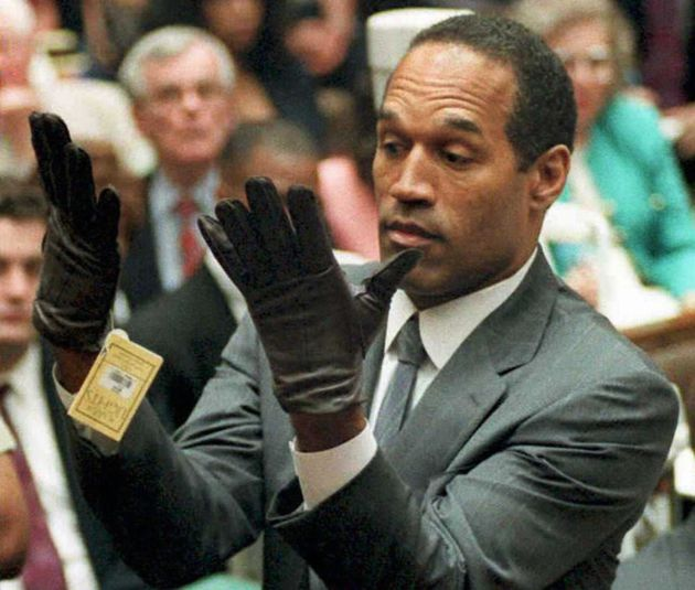 O.J. Simpson looking at a new pair of Aris extra-large gloves that prosecutors had him put on during his double-murder trial in Los Angeles. 1995.