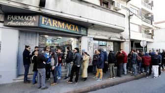 People queue in line outside of a pharmacy to buy legal marijuana in Montevideo, Uruguay July 19, 2017.  REUTERS/Andres Stapff